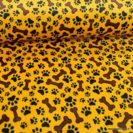 Tissu doudou motifs pattes de chien et os fond moutarde